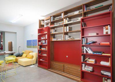 Parete attrezzata legno con librerie scorrevoli sovrapposte.